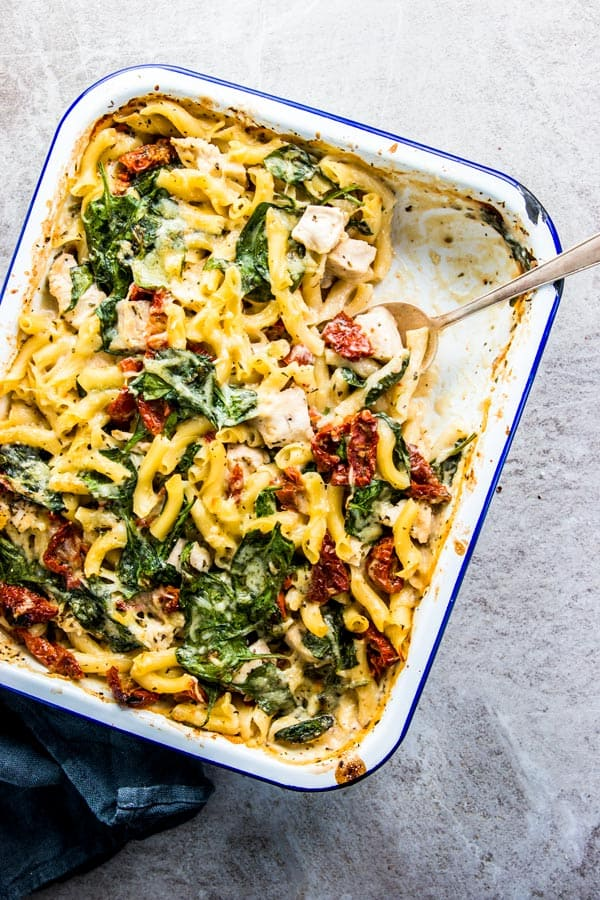 Chicken Florentine Pasta Casserole in a blue rimmed enamel dish with a silver spoon and black linen.