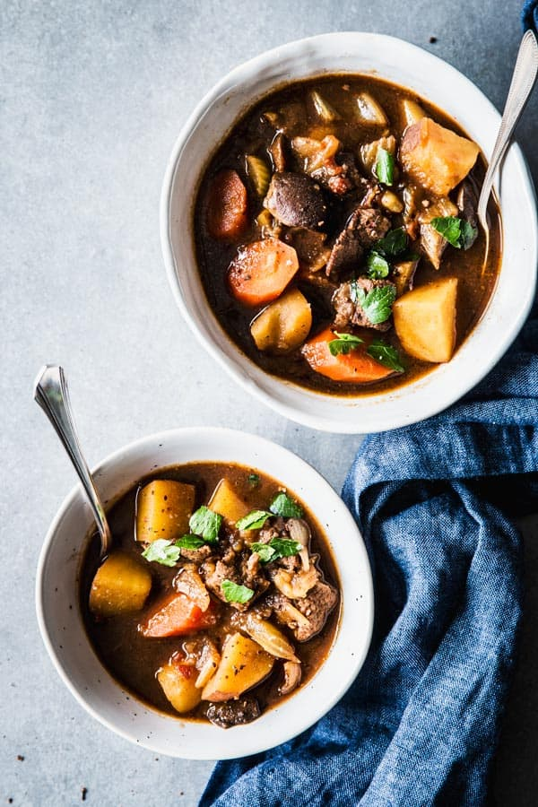 Two white bowls with beef stew, on a counter top with a blue linen.
