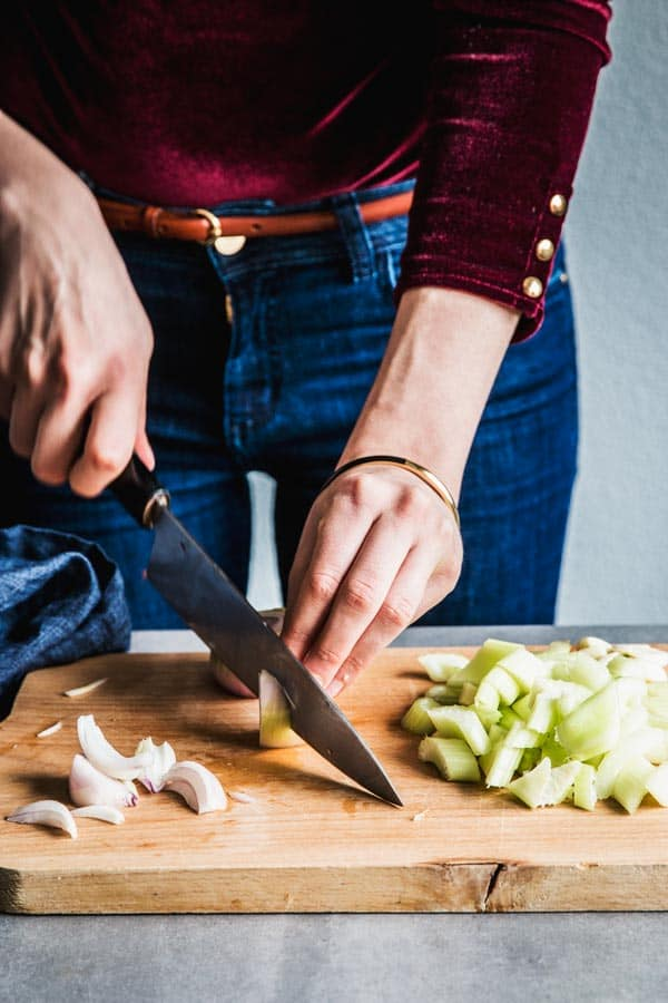 Woman in a red top slicing and onion on a wooden chopping board.