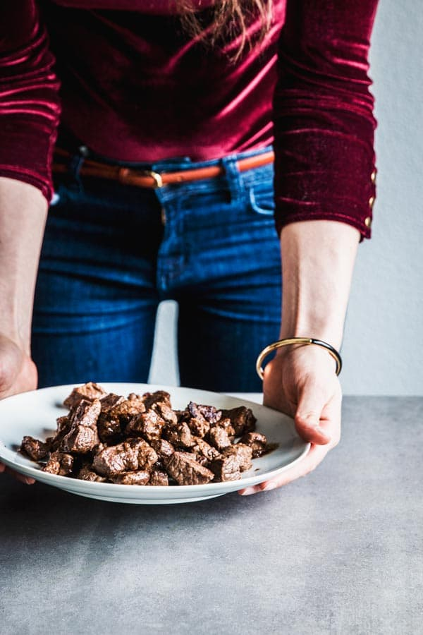 Woman holding a plate with browned beef chuck cubes.