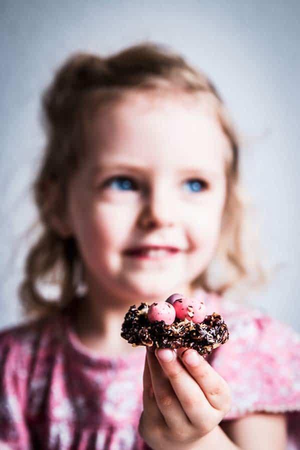 Girl holding a no bake bird's nest cookie.