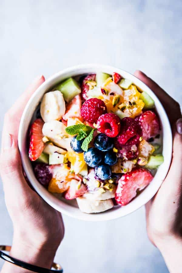 Holding a white bowl with Greek Yogurt Fruit Salad.