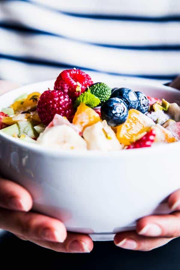 Woman in a striped shirt holding a bowl of Greek Yogurt Fruit Salad.
