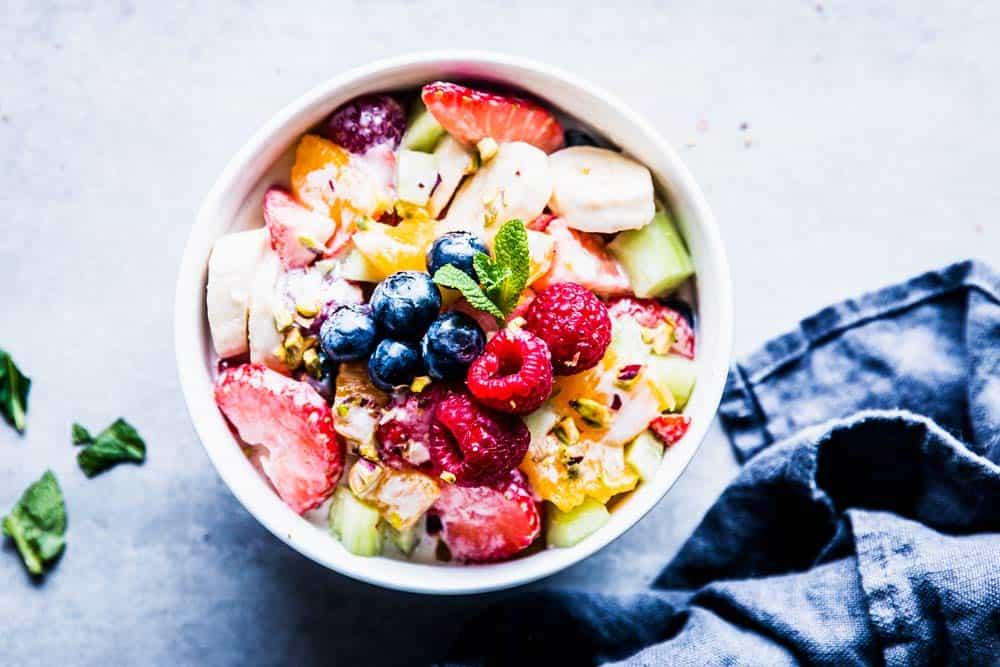 Greek Yogurt Fruit Salad in a white bowl with mint and a dark napkin.