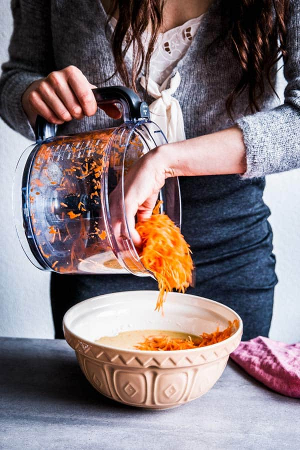 Woman adding shredded carrot to healthy carrot muffin batter.