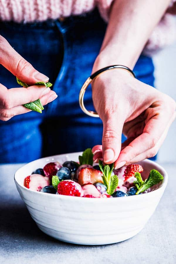 Woman adding fresh mint to a bowl of fruit salad.