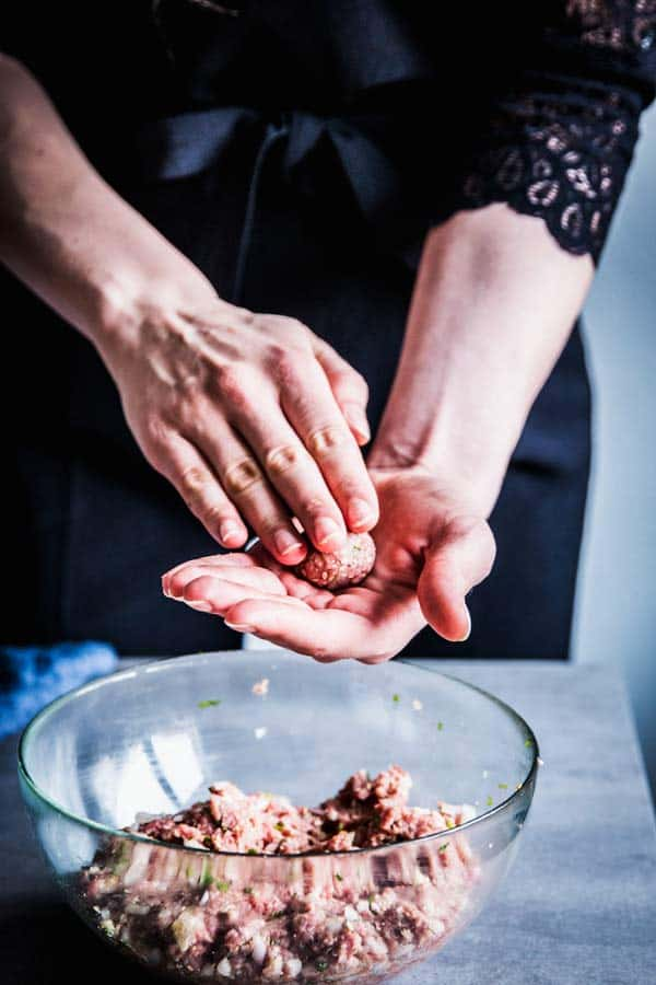 Woman in a black jumpsuit, making homemade meatballs.