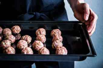 Woman in a black jumpsuit, holding a sheet pan full of homemade meatballs. Close up.