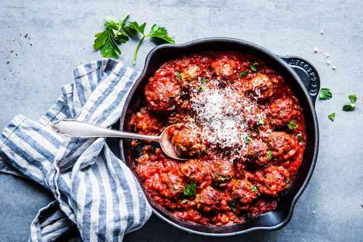 Photo of easy Italian meatballs in a black cast iron skillet with a spoon.