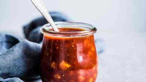 Pineapple BBQ Sauce in a small glass jar with a spoon and a black napkin on the table.