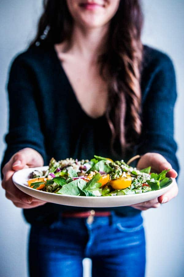 Woman in blue jeans and a black sweater holding a plate of quinoa spinach salad with asparagus.
