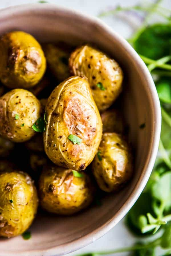 Roasted Baby Potatoes in a rose bowl with greens on the side.
