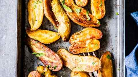 Roasted Fingerling Potatoes on a sheet pan with fresh parsley.
