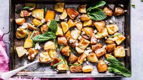 Roasted red potatoes with feta and mint on a baking sheet with a pink napkin.
