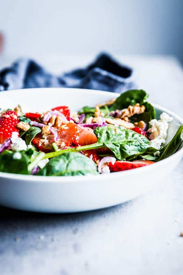 Spinach Strawberry Walnut Salad in a white bowl on the table.