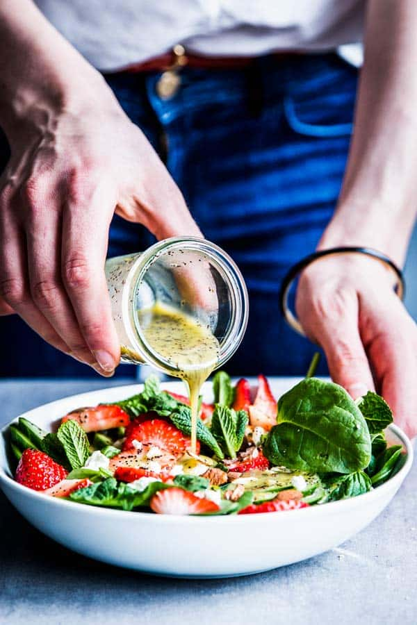 Woman in blue jeans ouring lemon poppy seed dressing over strawberry spinach salad.