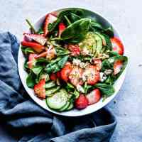 Strawberry Spinach Salad with Poppy Seed Dressing in a white bowl with a black napkin.