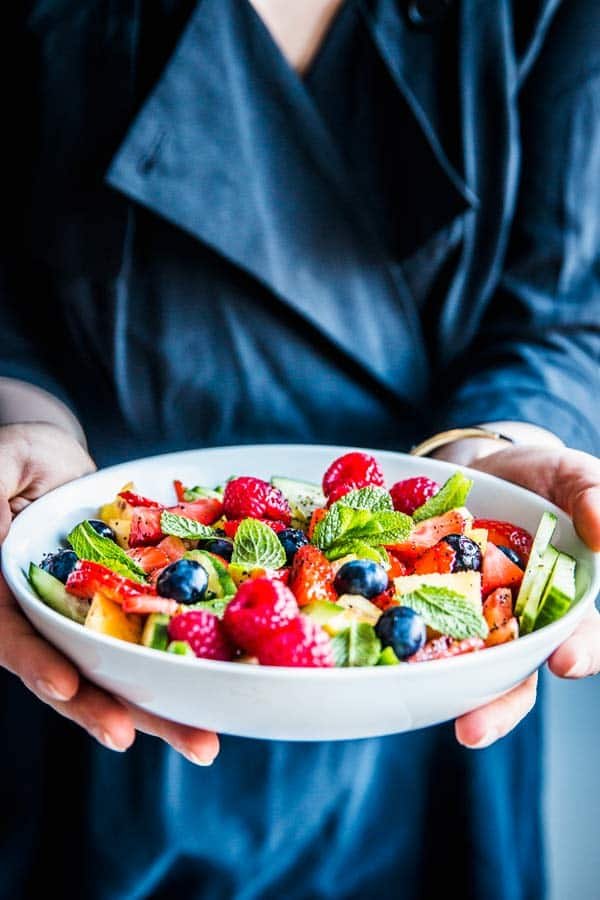 Woman holding a bowl of summer fruit salad.