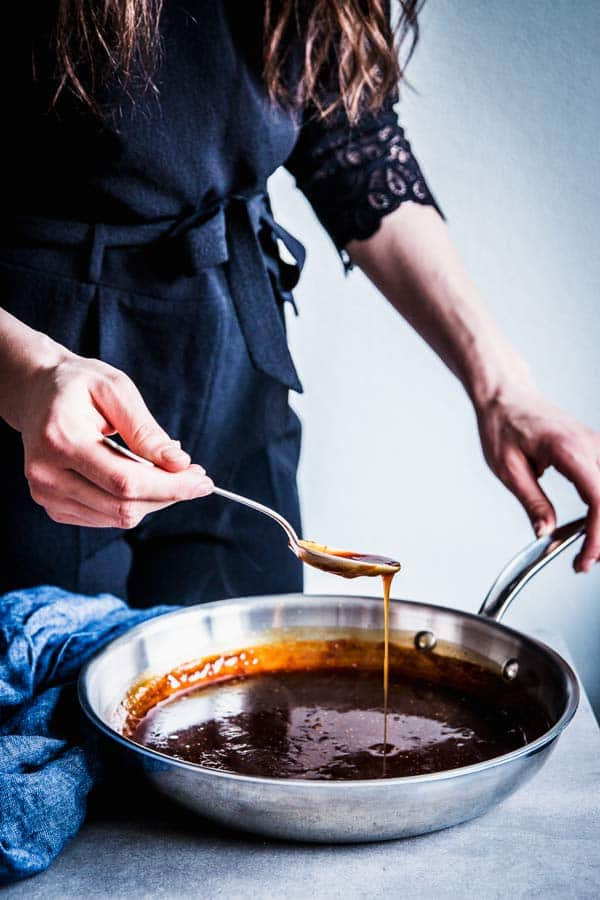 Woman in a black jumpsuit making teriyaki sauce.