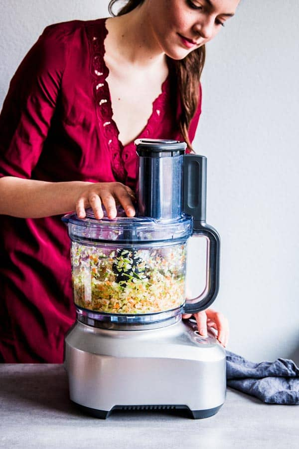 Woman chopping vegetables in a foodProcessor to make bbq turkey meatloaf