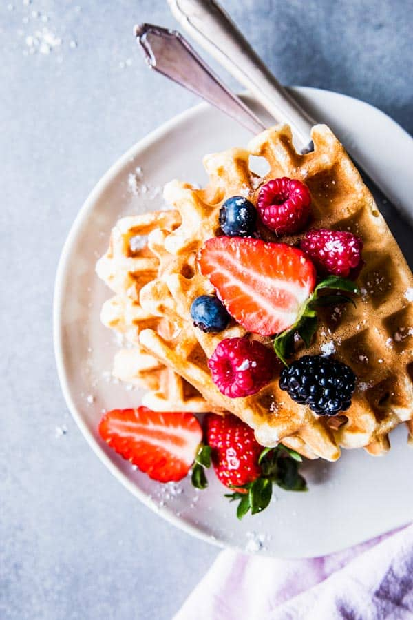 Buttermilk waffles on a white plate with cutlery, topped with mixed berries.