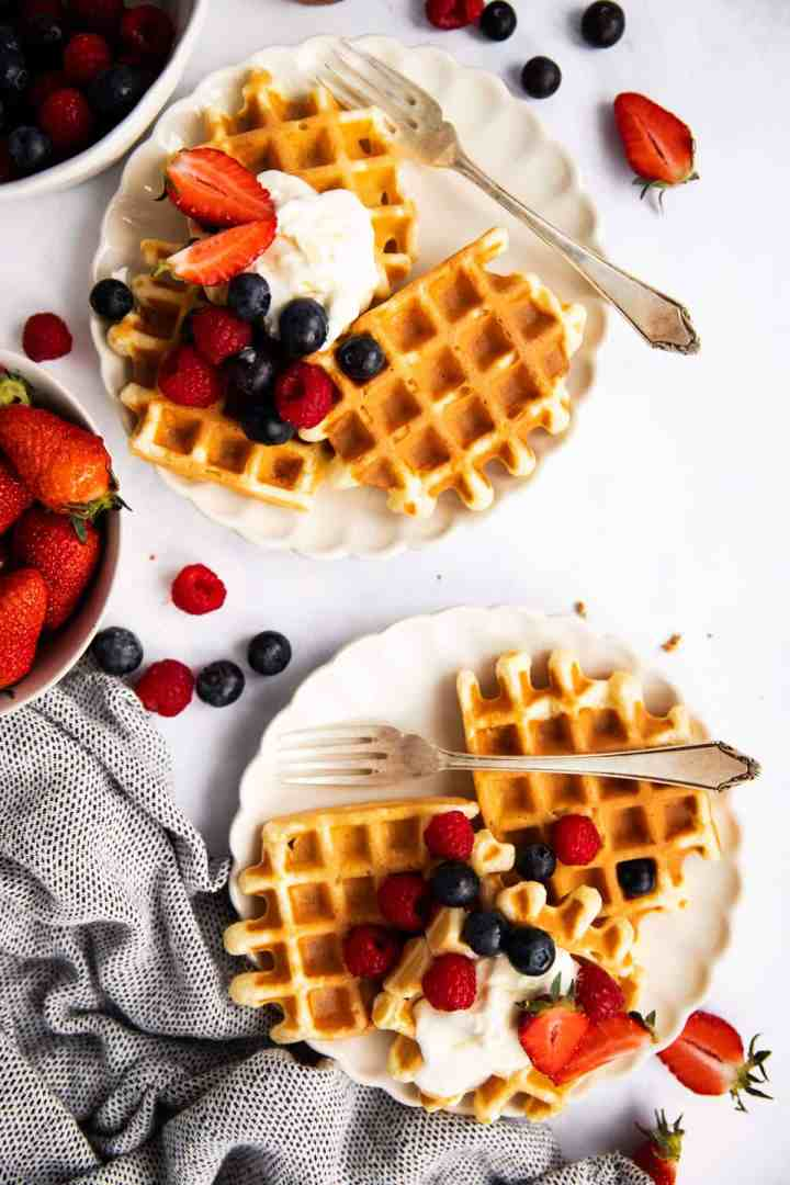 top down view on two plates with waffles and fresh fruit