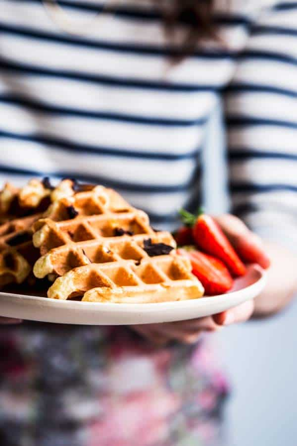 Woman in a striped shirt holding a plate with chocolate chip waffles.
