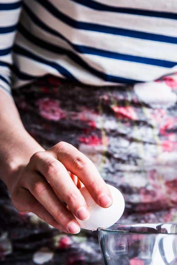 Woman cracking an egg.