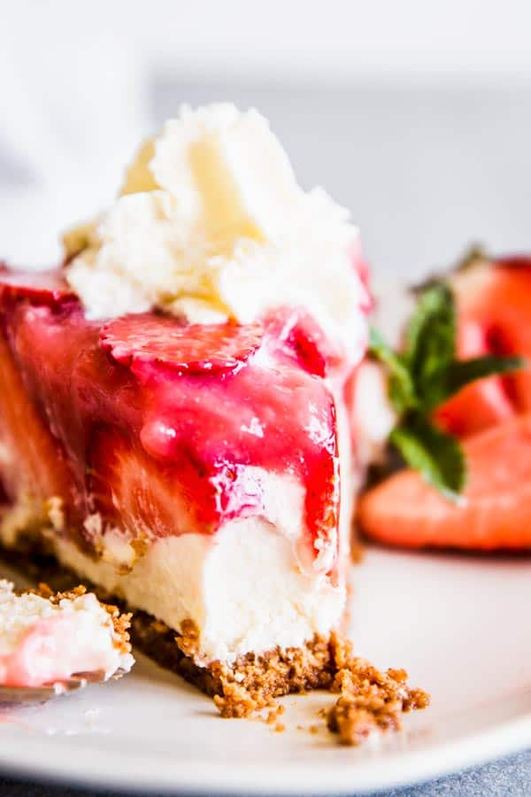 No bake strawberry cheesecake pie on a plate with whipped cream