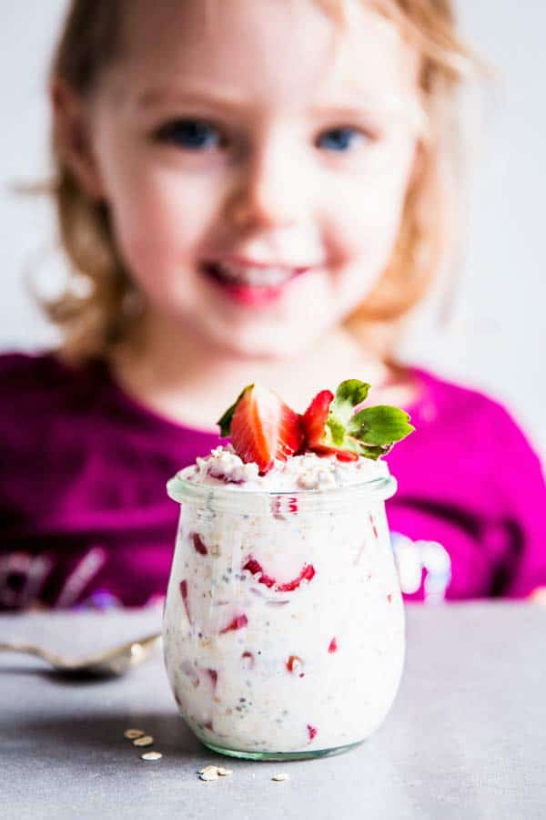 Girl with a jar of vanilla strawberry overnight oats.