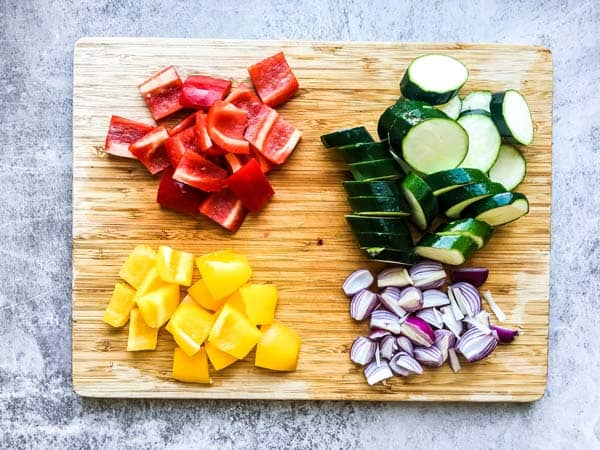 sliced vegetables on a wooden cutting board for greek chicken kabobs