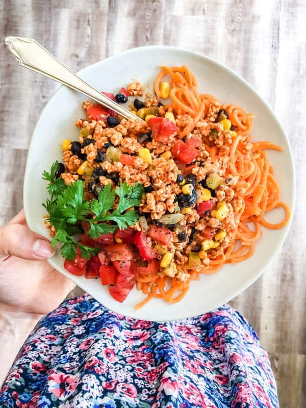 woman holding a plate with sweet potato turkey taco pasta