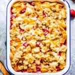 strawberry French toast casserole in a dish with fresh strawberries and a wooden spoon