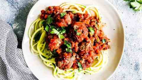 healthy Italian meatballs on a white plate with zucchini noodles and parsley