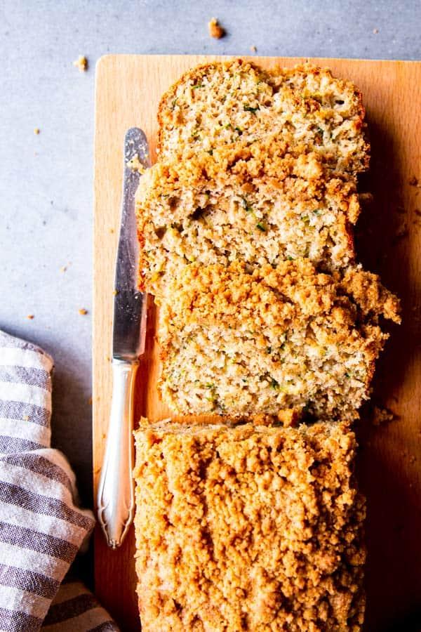 sliced cinnamon crunch zucchini bread on a wooden chopping board