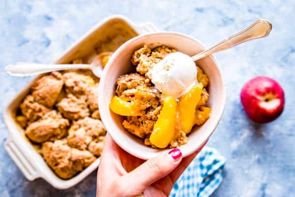 holding a bowl of peach cobbler with ice cream