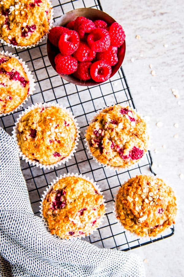 raspberry oatmeal muffins and fresh raspberries on a cooling rack