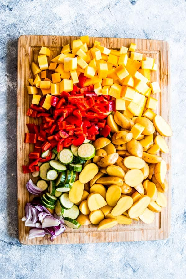 vegetables prepped on a chopping board for sausage and potato foil packets