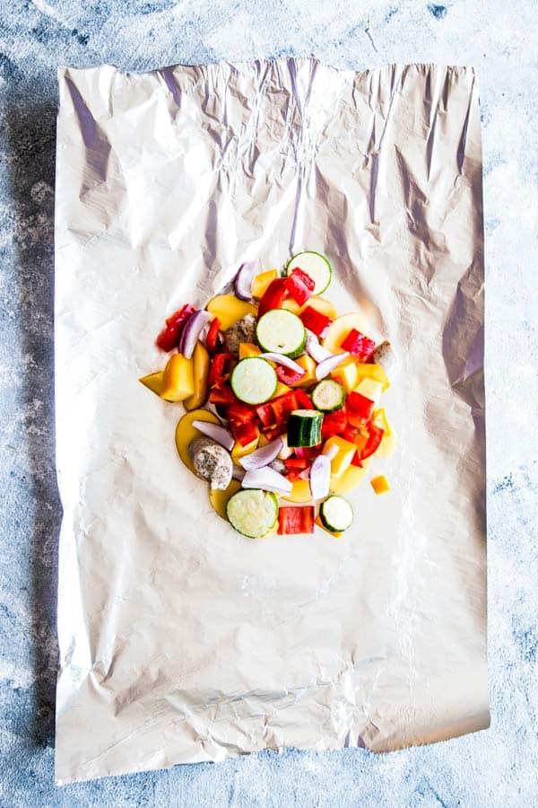 vegetables, sausage and potatoes on a piece of foil