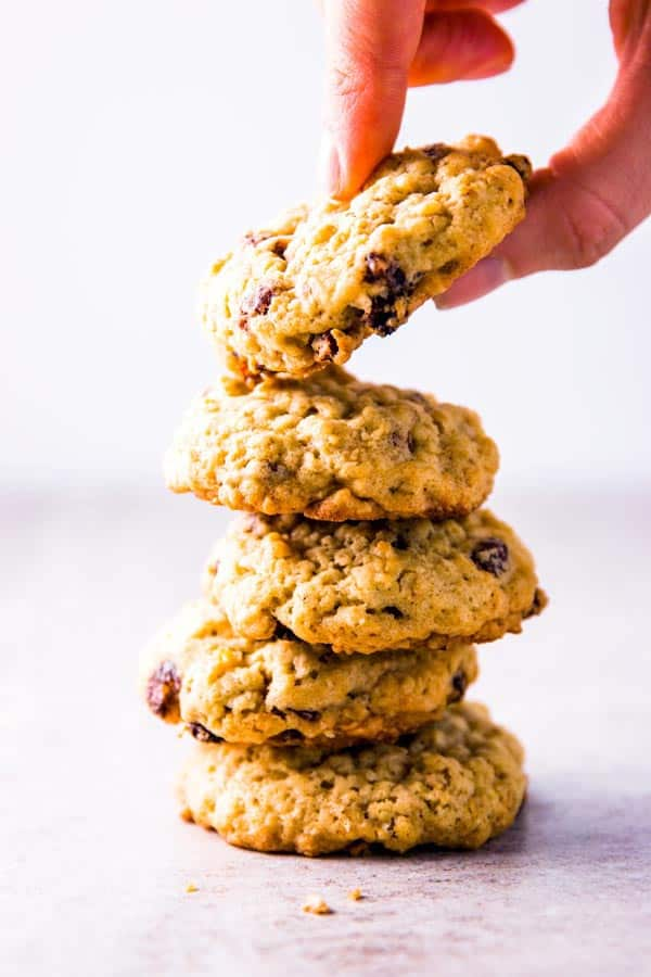 taking an oatmeal raisin cookie from a stack