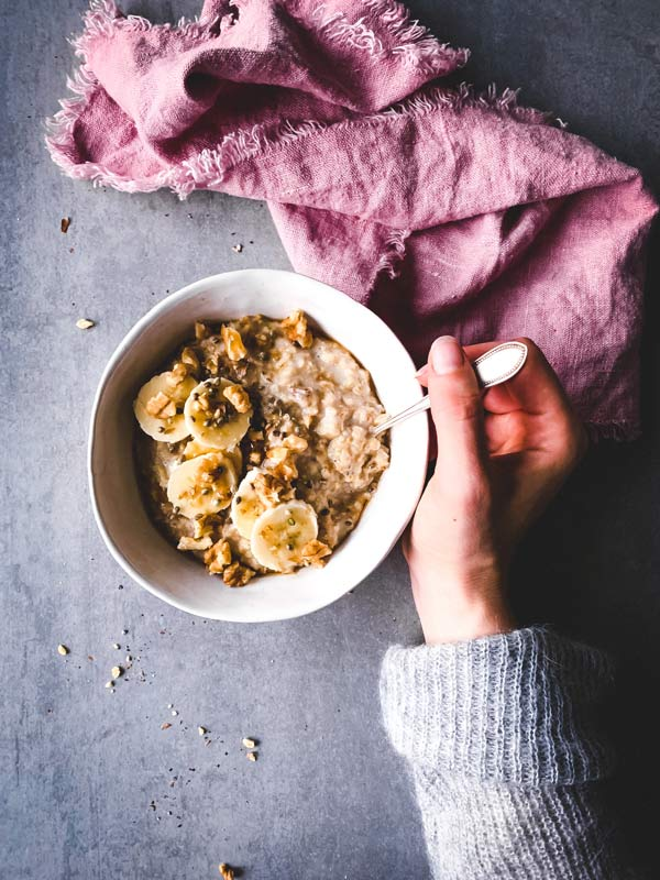woman holding a spoon in a bowl with walnut, date and banana oatmeal