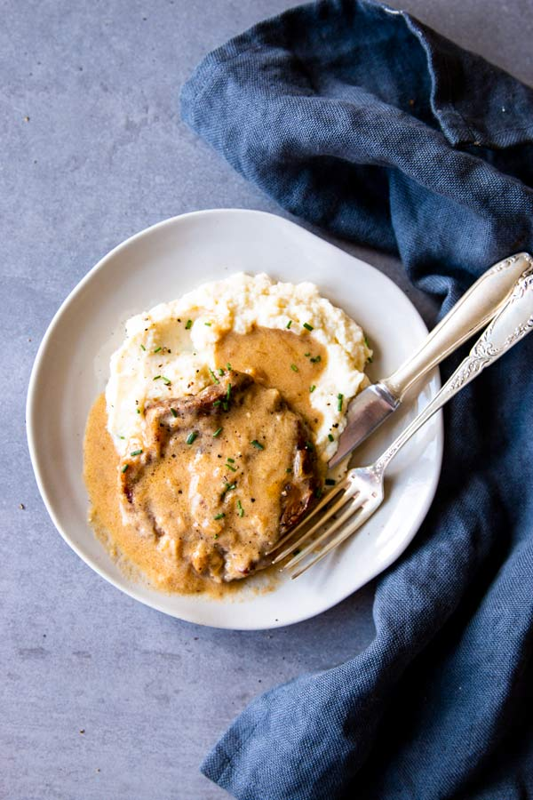 pork chops and mashed potatoes with sour cream sauce on a white plate