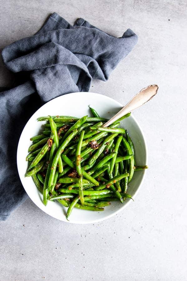 sautéed green beans in a white bowl