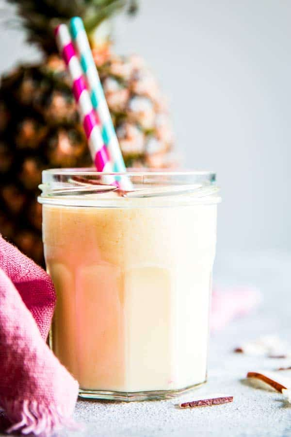 pina colada smoothie in a glass with straws and a fresh pineapple