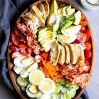 meal prep Cobb salad on a wooden platter with ranch dressing