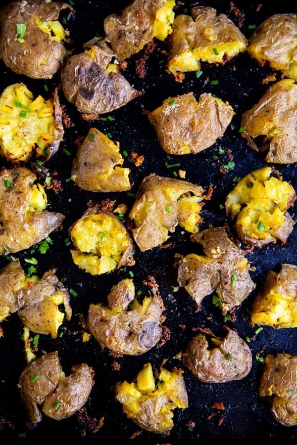 dark sheet pan with garlic smashed potatoes