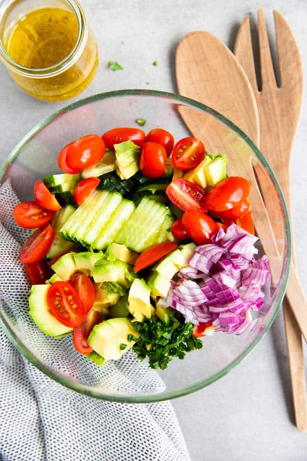 ingredients for cucumber tomato avocado salad in a bowl