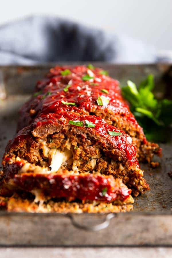sliced mozzarella stuffed meatloaf on a sheet pan