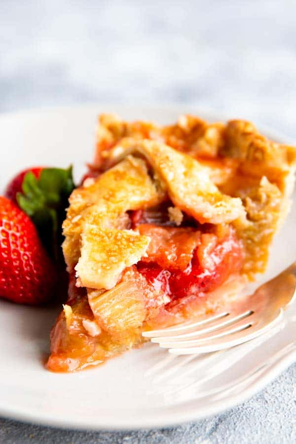 slice of strawberry rhubarb pie on a plate with a fresh strawberry