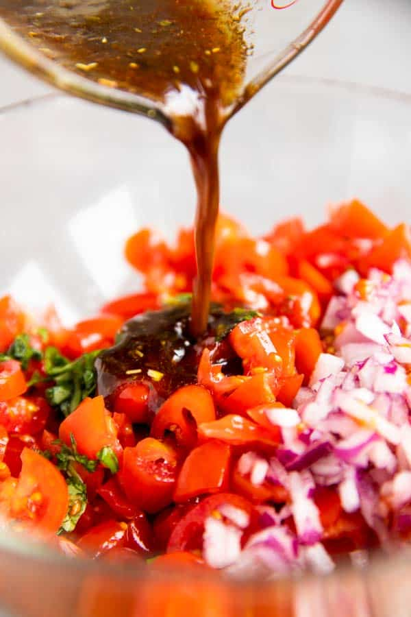 pouring balsamic dressing over bruschetta topping